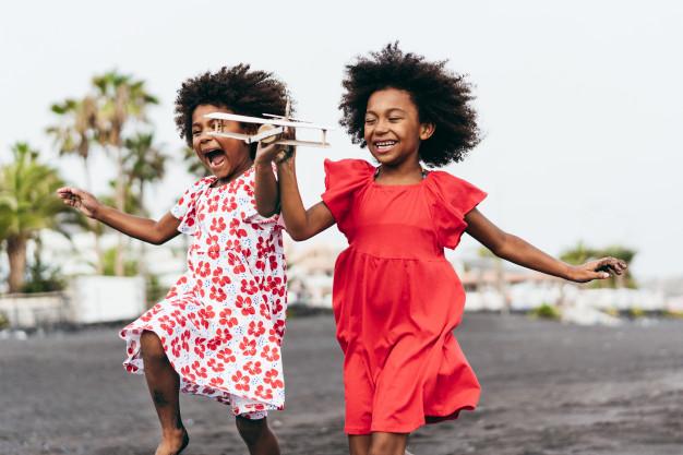 jumeaux-afro-soeurs-courir-plage-tout-jouant-avion-jouet-bois-mode-vie-jeunes-concept-voyage-accent-principal-visage-enfant-droit_166273-508